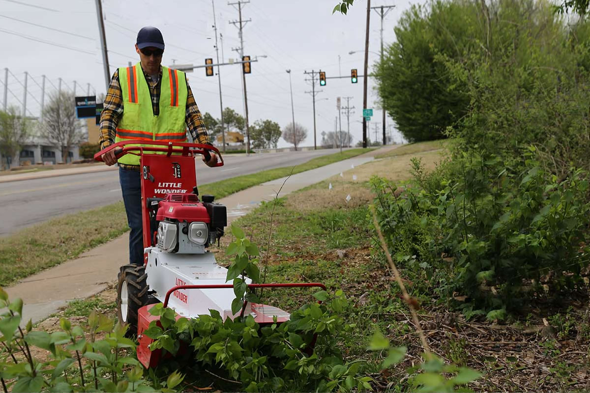Brush cutter clearing along sidewalk